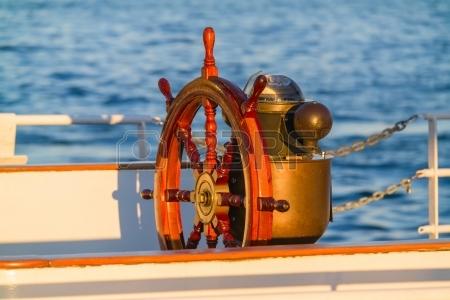 15157540-volante-e-bussola-su-una-vecchia-barca-a-vela-d-epoca-illuminata-dalla-luce-del-tramonto